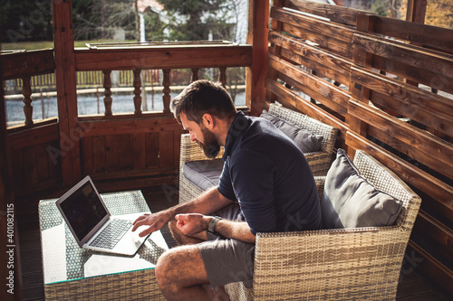 man working on laptop in wooden cottage Fotobehang