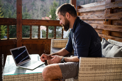 Leinwand Poster man working on laptop in wooden cottage