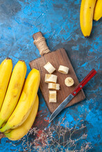 Vertical View Of Natural Split And Full Fresh Bananas On Wooden Cutting Board And Knife On Blue Isolated Background