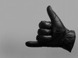 black leather glove shows drink gesture. isolated neutral background. copy space