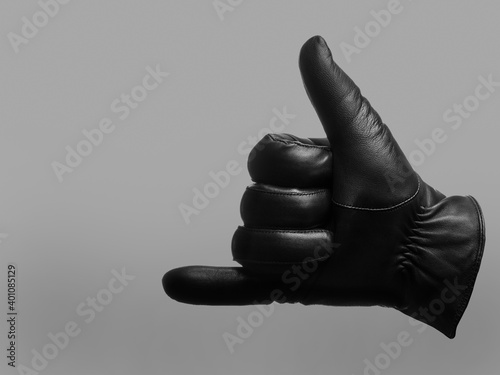 Fototapeta black leather glove shows drink gesture. isolated neutral background. copy space obraz