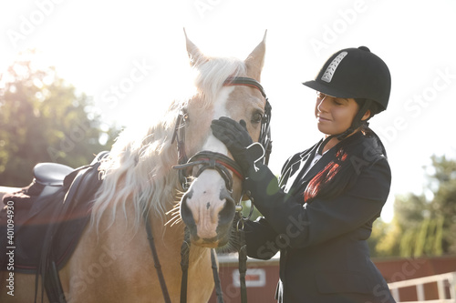 Canvas Young woman in horse riding suit and her beautiful pet outdoors on sunny day