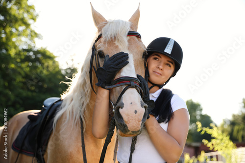 Young woman in horse riding suit and her beautiful pet outdoors on sunny day