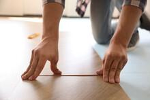 Worker Installing Laminated Wooden Floor Indoors, Closeup
