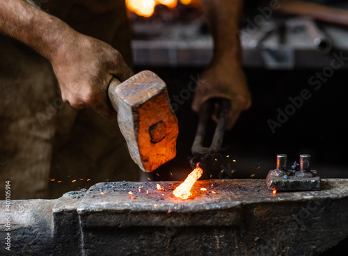 Fotografia Close up blacksmith working metal with hammer on the anvil in the forge