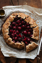Sliced Cherry Galette On Parchment Paper