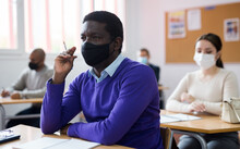 African-american Student Wearing Protective Mask Among Students In University Classroom