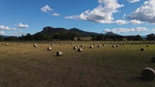 A Slow Moving Drone Video Flying Above Bales Of Hay Freshly Rolled With A Mountain Range In The Foreground