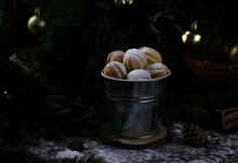 Cookies In The Form Of Nuts In A Metal Bucket In The Christmas Decorations, Sprinkled With Powdered Sugar