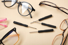 Eye Glasses And Small Screwdrivers On Beige Background, Broken Glasses, Glasses Repair Concept
