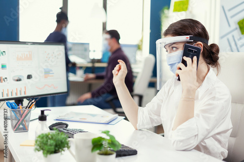 Obraz na plátně Business administrator sitting at her workplace wearing face mask during covid19 talking on smartphone