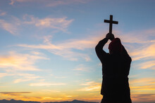 Silhouette Young Man Praying To The GOD While Holding A Crucifix Symbol With Bright Sunbeam On Top Mountain