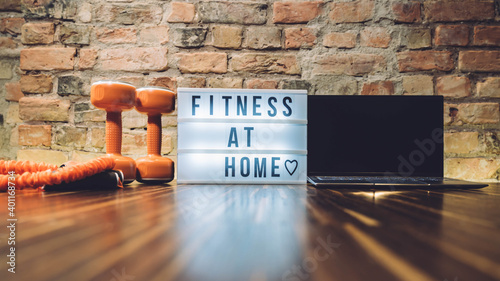 Sport equipment and lightbox with text FITNESS AT HOME on floor indoors. Message to promote self-isolation during COVID‑19 pandemic. Working out at home. Coronavirus COVID-19 Social distancing sign