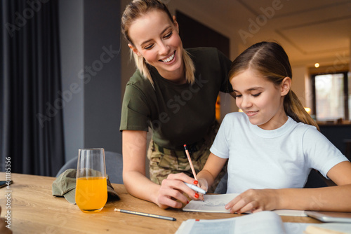 Beautiful happy military woman doing homework with her daughter at home