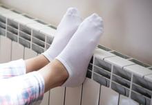 Woman's Legs In Socks On White Radiator Background