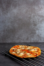 Vertical Frame Of A Mushroom Cheese Home Baked Supermarket Simple Pizza With Crunchy Crest And Golden Yellow Orange Tint Studio Low Key Still Life On A Metal Oven Grid In A Modern Gray Kitchen Counter
