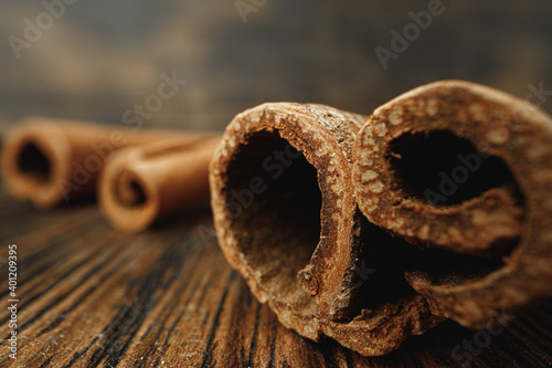 Fototapeta Macro photo of cinnamon sticks on wooden background obraz