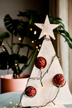 """A """"do It Yourself"""" Christmas Tree Made Of Wood. There Are Red Christmas Balls And Lights Decorating It. Behind It, There Is A Monstera Deliciosa. Shallow Depth Of Field."""