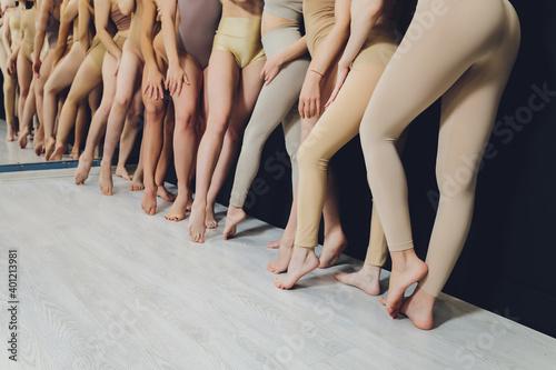 Fotografie, Obraz Many girls training in studio ballet, long woman legs ass bracing, wearing sexual flesh color bodysuit