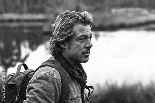 Obraz na plátně Man in jeans jacket with backpack near lake
