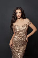 Beautiful Woman Celebrity With Makeup And Curly Hairstyle In Golden Evening Dress On Black Background