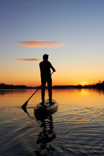 Rear View On Silhouette Of Stand Up Paddle Boarder Paddling At Sunset On River At Cold Time
