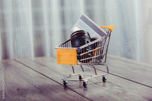 Obraz na plátne Lens camera shopping,lens and credit card in a shopping basket
