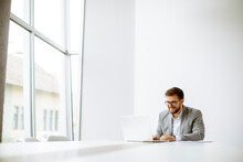 Young Man Working On Laptop In Bright Office
