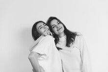Hugs. Portrait Of Beautiful Brunette Women In Comfortable Soft Longsleeves On Studio Background, Black And White. Home Comfort, Emotions, Facial Expression, Winter Mood Concept. Friendship.