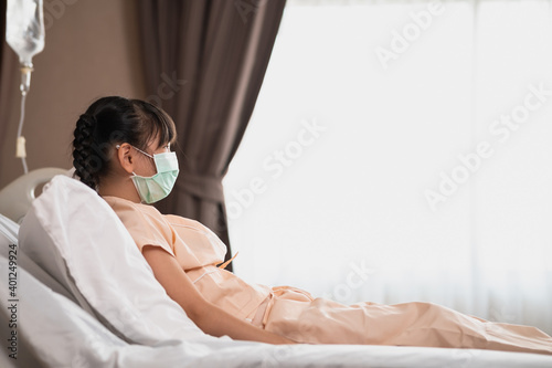 Obraz na plátne Recovering Asian girl wear surgical mask and sitting on hospital bed feeling sad and unhappy