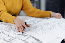Woman Working At Office With Blueprint And Documents