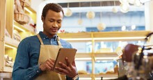 Close Up Of African American Happy Young Handsome Man Worker In Apron Stands In Bakery Shop, Texting And Typing On Tablet. Male Seller Browsing Online On Device. Business Concept. Retail Industry