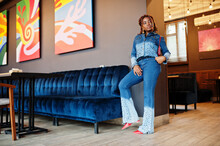 Lovely African American Woman With Dreadlocks In Blue Stylish Jeans Jacket At Cafe. Beautiful Cool Fashionable Black Young Girl Indoor.