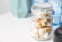 Jar With White Sugar Cubes And Brown Cane Sugar Lump On The White Kitchen Table. Dry Food Product On Home Kitchen