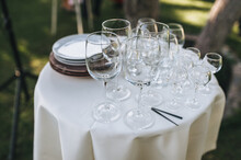 Glass Goblets And Plates Stand On A Round White Table Covered With A Tablecloth As Decorations For A Banquet Or Buffet Table.