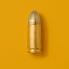 Gold Bullet On Yellow Background