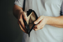 Empty Wallet In The Hands Of A Man At Home. Poverty Concept, Crisis. Dismissal, No Earnings