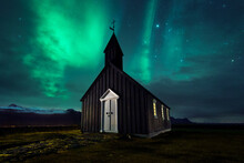 Magnificent Scenery Of Wooden Church Located On Meadow On Background Of Sky With Aurora Borealis Phenomenon In Iceland At Night