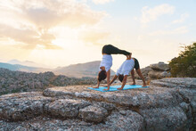 Full Body Of Unrecognizable Couple Practicing Acro Yoga And Man Doing Downward Facing Dog Pose While Woman Performing Handstand On Top Of Rock In Mountainous Terrain