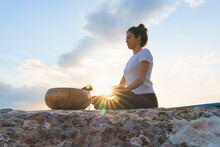 From Below Side View Of Concentrated Serene Young Female Sitting In Lotus Pose With Mudra Gesture On Top Of Rocky Mountain And Practicing Yoga Meditation