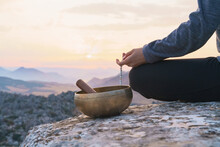 Back View Of Crop Anonymous Female Holding Beads While Sitting Near Tibetan Singing Bowl And Meditating On Top Of Rocky Mountain At Sunset