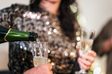 Unrecognizable Female In Elegant Shiny Dress Standing In Room And Pouring Cold Champagne In Glass Of Anonymous Person During Christmas Party