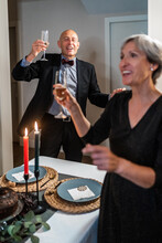 People With Champagne Glasses During Christmas Party At Home Having Fun