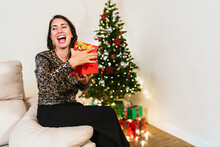 Side View Of Excited Female In Elegant Dress Opening Box And Enjoying Gift During Christmas Celebration At Home