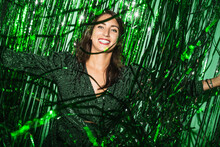 Delighted Female Wearing Festive Dress Playing With Green Shiny Tinsel Stripes At Party While Looking At Camera