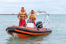 Young Lifeguards In Orange Life Vest Standing On Modern Motorboat On Calm Rippling Seawater And Looking At Camera