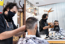 Barber In Black Protective Mask Cutting Hair Of Middle Aged Bearded Hipster Male Client Sitting In Chair In Front Of Mirror In Barbershop