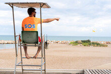 Back View Of Unrecognizable Male Employee On Lifeguard Tower Above Ocean