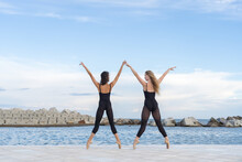 Back View Full Body Of Talented Slim Female Dancers In Similar Black Leotards Standing On Tiptoe With Outstretched Arms While Performing Dance Movement Together On Sea Embankment