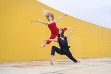 Full Body Of Talented Young Female Dancers In Stylish Colorful Clothes Jumping And Performing Graceful Dynamic Movement Near Yellow Wall On Street
